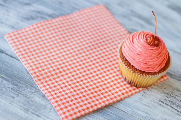 Petit gâteau rose et baie rouge de serviette sur la confiserie colorée de glaçage dans le dessert cuit au four simple de café local