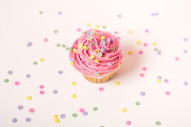 Petit gâteau rose avec une bougie allumée