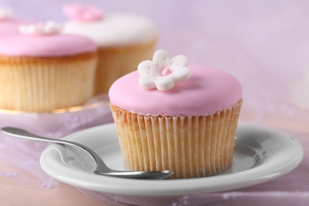 Petit gâteau savoureux sur la soucoupe sur le rose