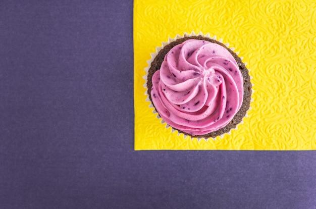 Petit gâteau violet sur une serviette jaune et sur un bleu