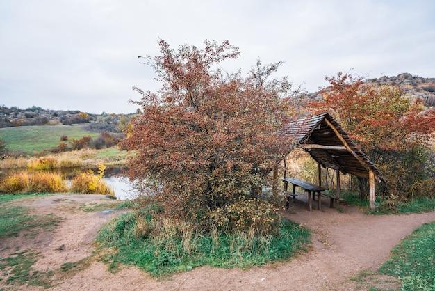 Un petit gazebo mignon en bois parmi de beaux arbres d'automne dans la nature des collines des carpates