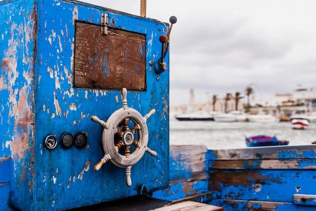 Petit gouvernail en bois d'un bateau échoué vieilli et abandonné au bord de la mer.