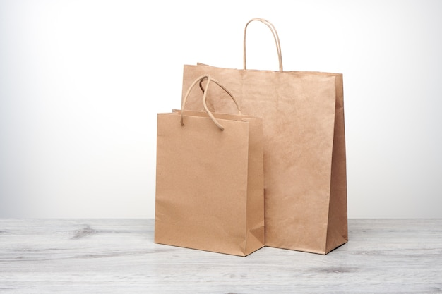 Petit et grand sac en papier avec poignées isolées. maquette de sac en papier kraft sur table en bois. sac à provisions recyclé pour la livraison à domicile de produits ou de nourriture.
