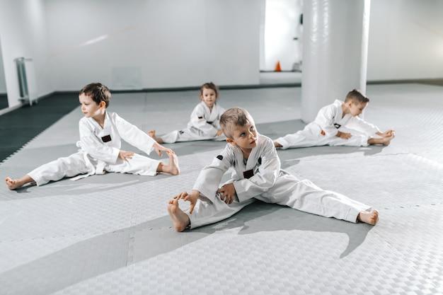 Petit groupe d'enfants sportifs caucasiens qui s'étirent et s'échauffent avant leur entraînement de taekwondo.