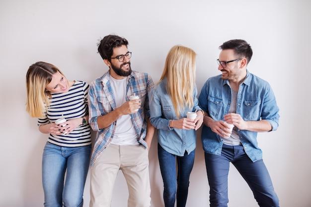 Petit groupe de jeunes hommes d'affaires détenant du café pour aller et des téléphones intelligents tout en parlant et en riant