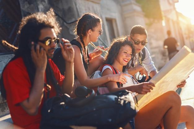 Petit groupe de touristes multiculturels assis à marches sur rue et regardant la carte. au premier plan gars de race mixte parler sur téléphone intelligent. heure d'été.