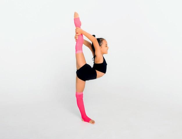 Le petit gymnaste sur un grand cube blanc exécute des exercices de sports