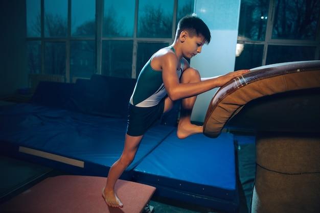 Petit gymnaste masculin s'entraînant dans une salle de sport flexible et actif