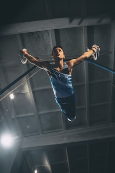 Petit gymnaste masculin s'entraînant en salle de sport, composé et actif. petit garçon en forme de race blanche, athlète en vêtements de sport pratiquant des exercices de force, d'équilibre. mouvement, action, mouvement, concept dynamique