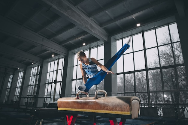 Petit gymnaste masculin s'entraînant en salle de sport, composé et actif.