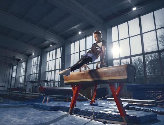Petit gymnaste masculin s'entraînant en salle de sport, flexible et actif. petit garçon en forme de race blanche, athlète en vêtements de sport pratiquant des exercices de force, d'équilibre. mouvement, action, mouvement, concept dynamique.