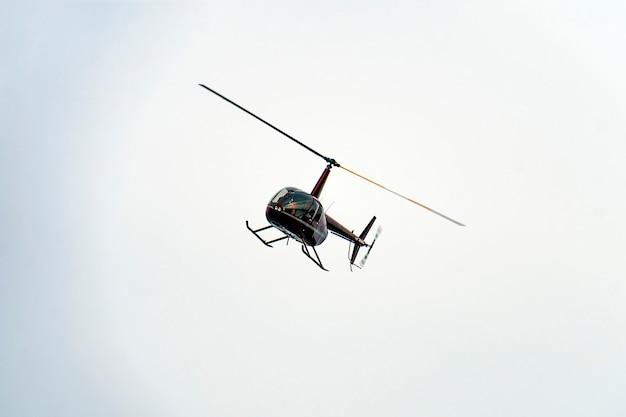Un petit hélicoptère rouge volant dans le ciel