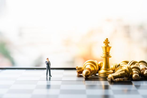 Petit homme d'affaires figure debout et marche sur l'échiquier avec des pièces d'échecs.