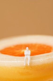 Petit homme assis au bord d'un cocktail margarita orange