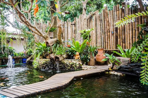Petit jardin avec bassin de poissons koi et mur de bambou décoré