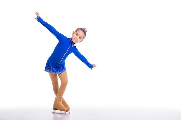 Un petit jeune patineur artistique posant en robe d'entraînement bleue sur la glace sur fond blanc