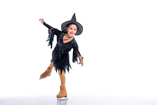 Petit jeune patineur posant en costume de sorcière d'halloween sur la patinoire sur fond blanc