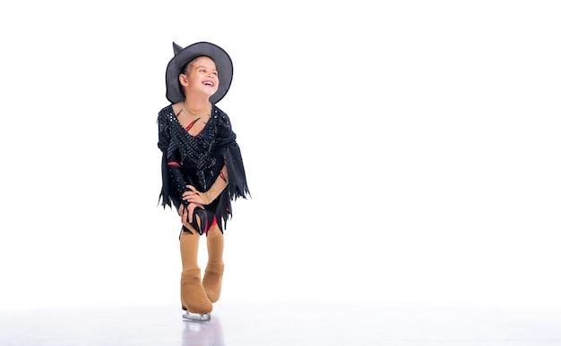Petit jeune patineur posant en costume de sorcière pour halloween sur glace sur fond blanc