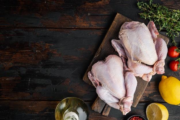 Petit jeune poulet entier cru avec des ingrédients, sur une vieille table en bois, vue de dessus
