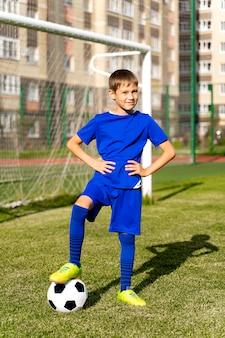 Un petit joueur de football avec un ballon se dresse sur un terrain de football vert dans le but