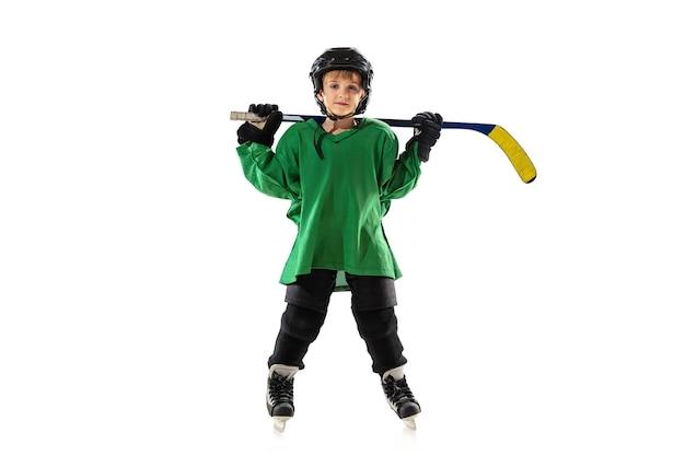 Petit joueur de hockey avec le bâton sur le court de glace, mur de studio blanc