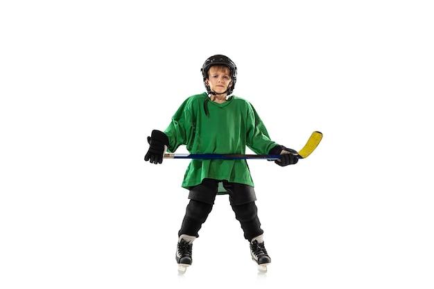Petit joueur de hockey avec le bâton sur un court de glace
