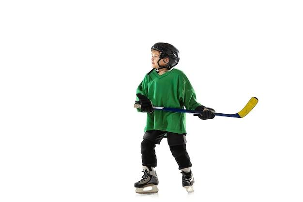 Petit joueur de hockey avec le bâton sur la patinoire, fond de studio blanc. sportsboy portant un équipement et un casque, s'entraînant, s'entraînant. concept de sport, mode de vie sain, mouvement, mouvement, action.