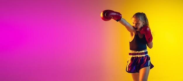 Petit kick boxer s'entraînant sur fond dégradé en néon