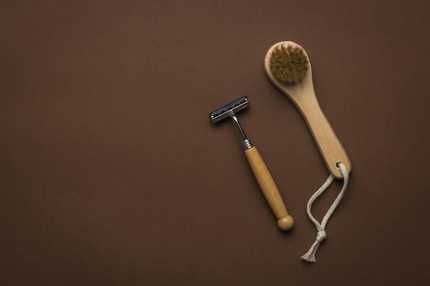 Un petit masseur facial à main et un rasoir avec un manche en bois sur fond marron. mise à plat. place pour le texte.