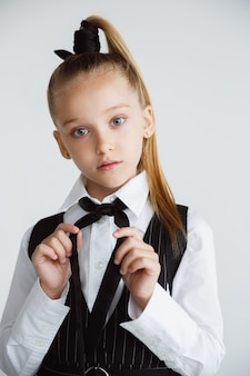 Petit modèle caucasien féminin posant en uniforme scolaire sur fond blanc.