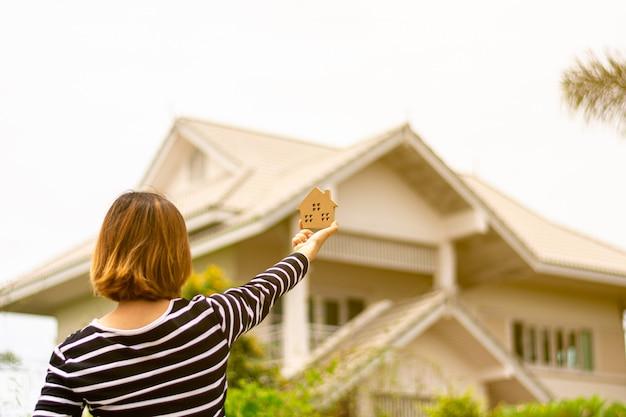 Petit modèle de maison en main de femme devant une maison.