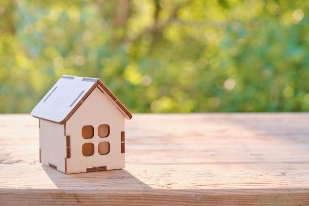 Petit modèle de maison sur table en bois avec fond abstrait nature bokeh vert. concept de vie de famille et d'immobilier d'entreprise.