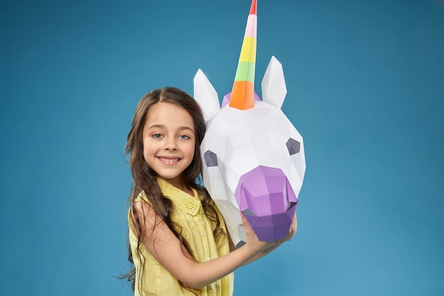 Petit modèle posant avec unicorme 3d blanc.
