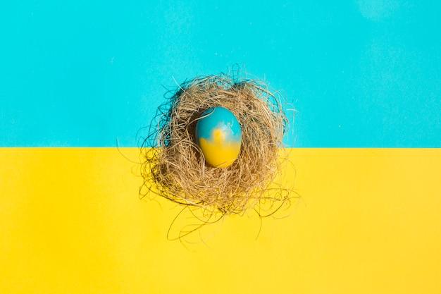 Petit oeuf de pâques en nid sur table