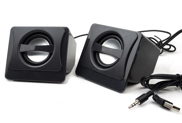 Petit ordinateur haut-parleurs noirs sur fond blanc.