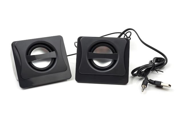 Petit ordinateur noir haut-parleurs sur fond blanc.