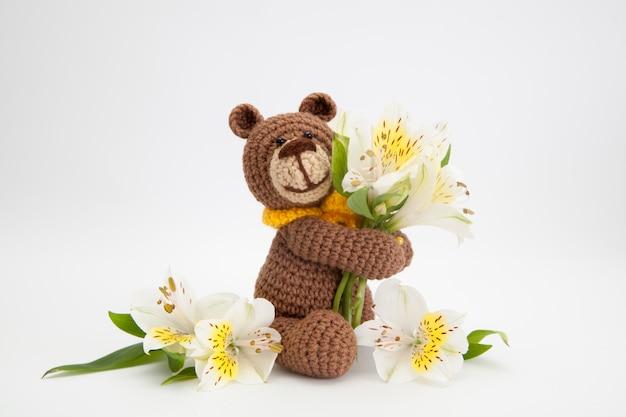 Petit ours brun à fleurs blanches, jouet tricoté, fait main. amigurumi.