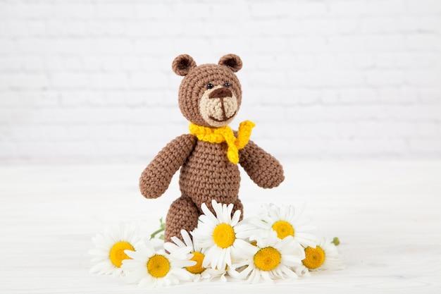 Un petit ours brun tricoté avec une écharpe jaune à la camomille sur fond blanc.