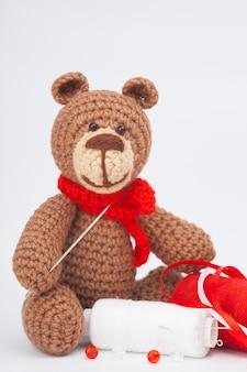 Petit ours brun tricoté avec des objets pour les travaux d'aiguille. aiguille, fil, perles. fait à la main, gros plan. amigurumi