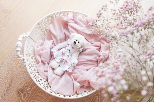 Petit ours en peluche blanc dans un panier sur plancher en bois. ours en peluche mignon dans un panier de travail ouvert blanc. couleurs blanches et roses