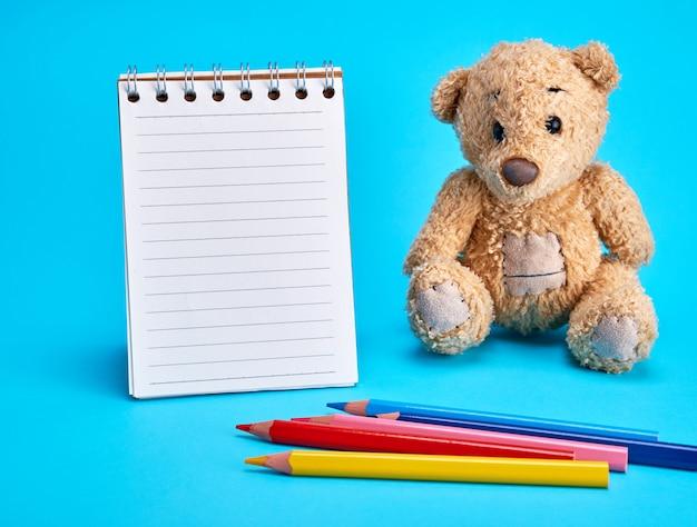 Petit ours en peluche marron et un cahier vierge