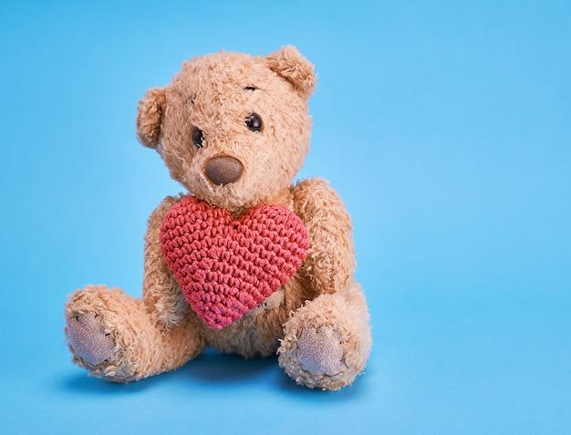 Petit ours en peluche tenant un coeur rouge