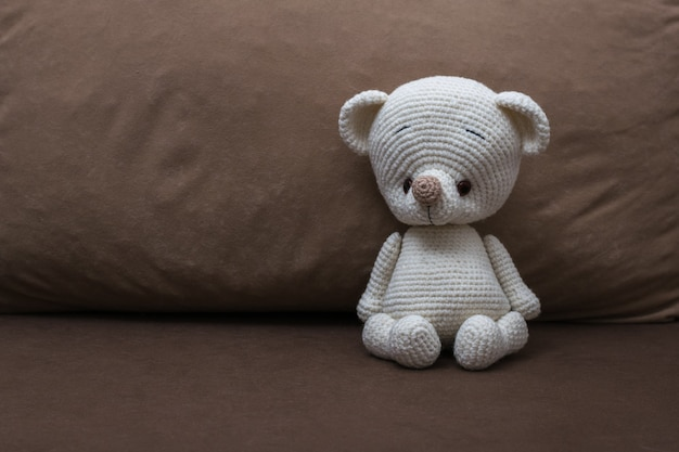 Un petit ours en tricot blanc sur un canapé moelleux. beau jouet tricoté.