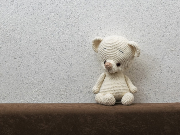Un petit ourson solitaire sur le dos du canapé contre le mur gris. beau jouet tricoté.