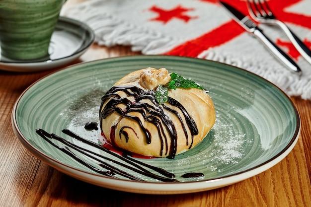 Petit pain appétissant fourré de baies juteuses saupoudrées de sucre en poudre, servi avec une vinaigrette au chocolat et des feuilles de menthe fraîche dans un restaurant géorgien sur fond avec le drapeau national des cinq croix