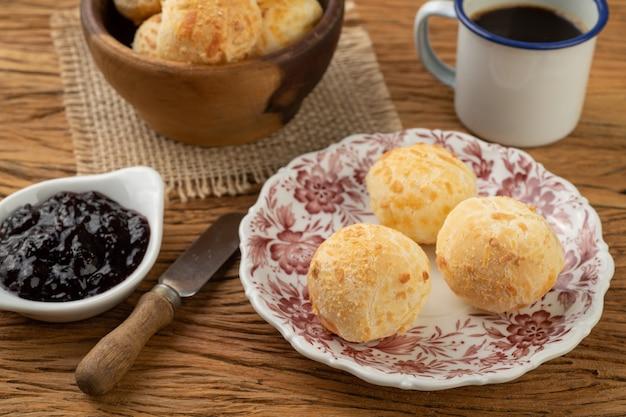 Petit pain au fromage brésilien typique dans un panier, café et confiture.