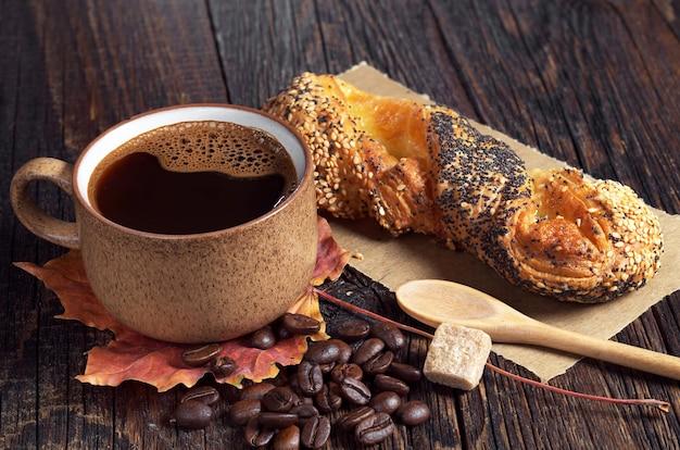 Petit pain aux graines de lin et pavot et tasse de café chaud sur la table