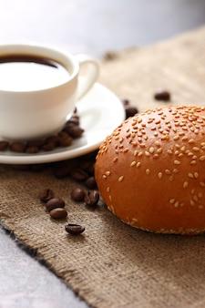 Petit pain aux graines de sésame, tasse blanche remplie de café sur une soucoupe et grains de café épars sur la vue de dessus de nappe de jute.