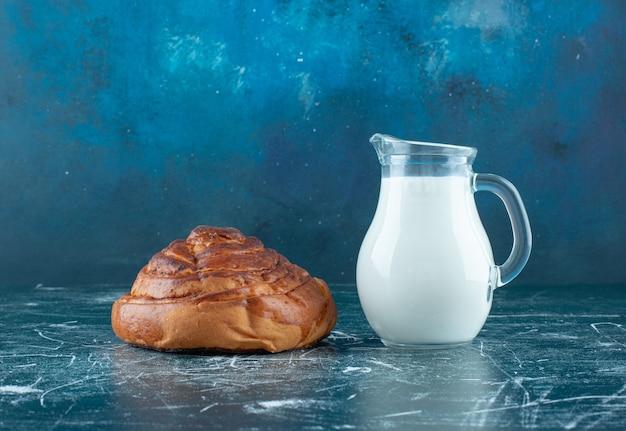 Un petit pain à la cannelle avec un pot de lait de côté. photo de haute qualité