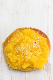 Petit pain à la crème de noix de coco sur une surface blanche
